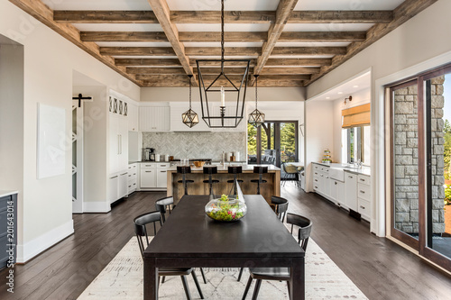 Stunning dining room and kitchen in new luxury home.Wood beams and elegant pendant lights accent this beautiful open-plan dining room and kitchen