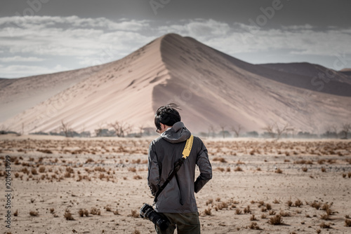 Young male photographer and traveler standing in front of sand dune in desert of Namibia, Africa - 201643099
