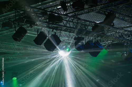 Stage lights. Soffits. Concert light. Silver mirror disco ball in the rays of the spotlights - 201643866