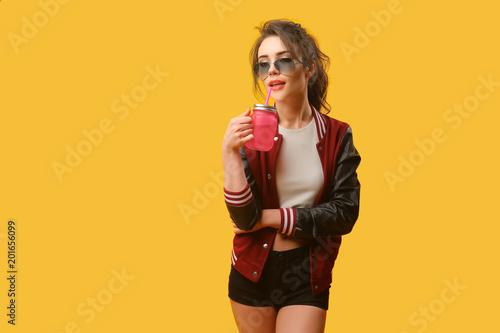 Gorąca kobieta pozuje w eleganckiej kurtce z pić słoju na żółtym tle.