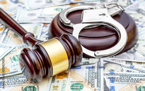 Judge's gavel with handcuffs on the background of dollar bills.