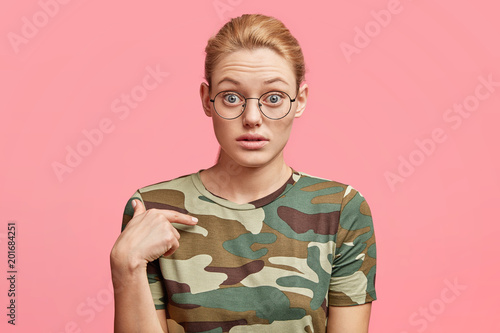 Isolated shot of stunned attractive female indicates at new t shirt, being surprised with high price on clothes in shopping mall, poses against pink studio background. Clothing, advertisment concept
