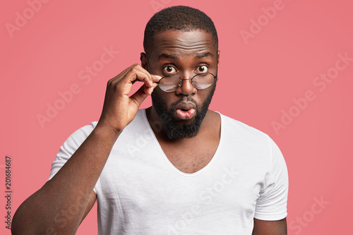 Portrait of surprised African male boss listens attentively colleague`s business presentation, being stupefied with annual figures, stands against pink background, wears spectacles and white t shirt