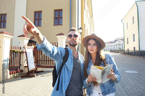 Foto Murales Happy couple walking outdoors sightseeing and holding a map.