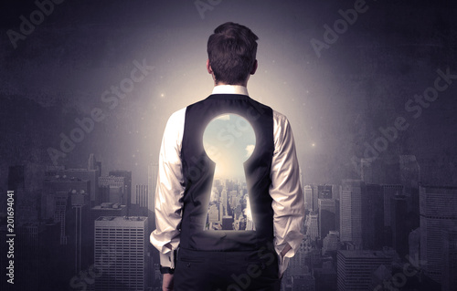 Foto Murales Young businessman standing and thinking with keyhole on his back and city graphic around
