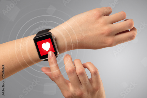 Foto Murales Naked female hand with smartwatch and with heart rate icon on the watch