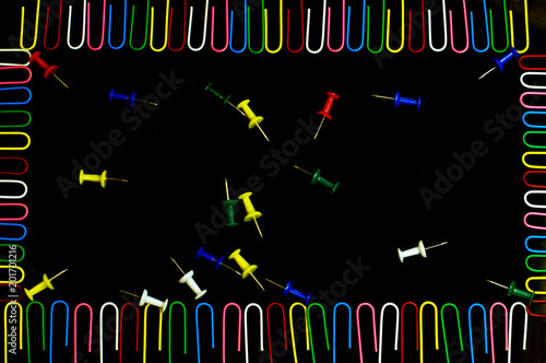 Foto Murales stationery paper clips and buttons of different colors lie on a black background