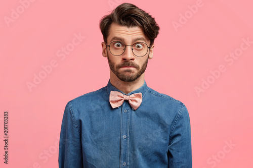 Fototapeta Portrait of irritated male student with shocked expression, has trendy haircut, wears glasses and elegant clothes, tries to control emotions, being angry with professor for bad evaluation of project