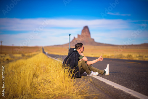 Canvas Arizona Tired hitch-hiker with suitcase sitting on a road