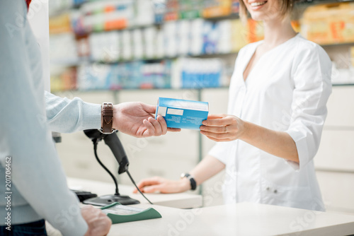 Giving madication at the pharmacy counter - 201706462