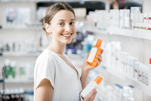 Foto Murales Woman choosing sunscreen lotion at the pharmacy