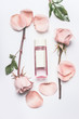 Pink cosmetic bottle with facial roses water or toner with essential oil , flowers and petals on white desk background, top view, branding mock up and copy space. Roses essence