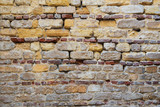 Background of irregular pattern of yellowish, red and gray grunge weathered uneven bricks stone wall surface