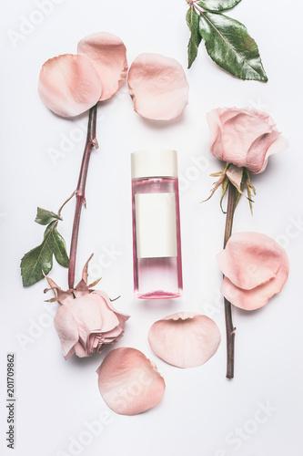 Różowa kosmetyczna butelka z twarzowymi różami nawadnia lub tonuje z istotnym olejem, kwiatami i płatkami na białym biurka tle, odgórny widok, oznakuje egzamin próbnego up i kopiuje przestrzeń. Esencja róż