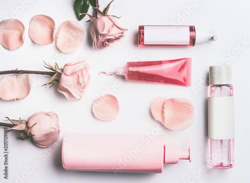Różowe naturalne produkty kosmetyczne z róż olejek eteryczny: żel, balsam, serum i toner róże butelek wody i rurki z brandingu makiety na białym tle biurko z kwiatami i płatkami, widok z góry