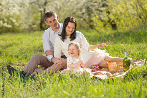 Foto Murales Happy parents with a child on a picnic in the blossoming spring gardens