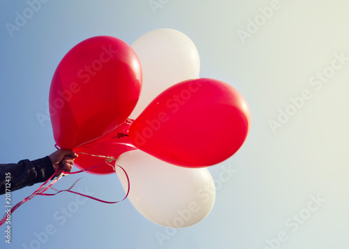 Red and white balloons in a hand against the background of the sky