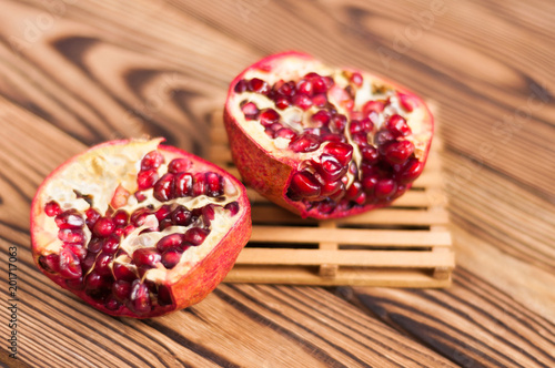 One half of red fresh ripe pomegranate with seeds on pallet beside one piece of pomegranate on old brown weathered wooden planks