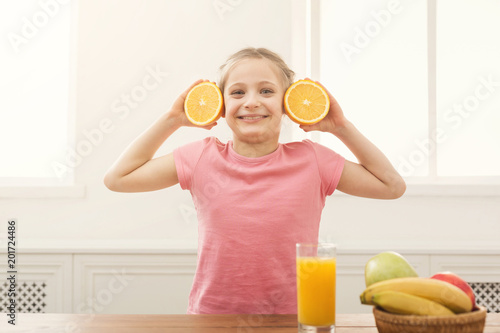 Happy little girl having fun with oranges over window