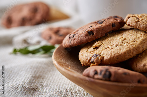 Foto Murales Side view of chocolate chip cookies on a wooden plate over rustic background, selective focus