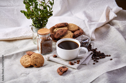 Wall mural Morning coffee in white cup, chocolate chips cookies on cutting board close-up, selective focus