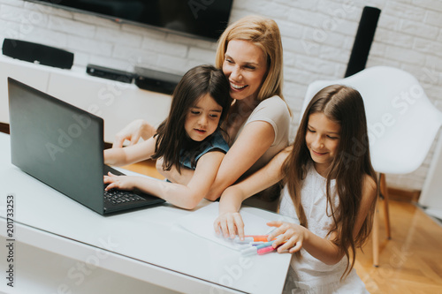 Foto Murales Mother and daughters in the room surfing on the laptop at home
