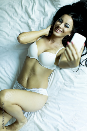 Pretty young woman taking selfie with mobile phone in the bed