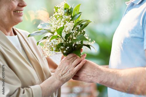 Foto Murales Bunch of tender white flowers in hands of senior spouses as symbol of romantic love