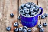 Fresh ripe blueberries and in blue enamel mug - 201744831