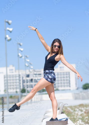 young ballerina dances and jumps on the street of a city