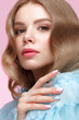 Beautiful girl with light make-up and gentle manicure in blue clothes. Beauty face. Design nails. Photo taken in studio on pink background