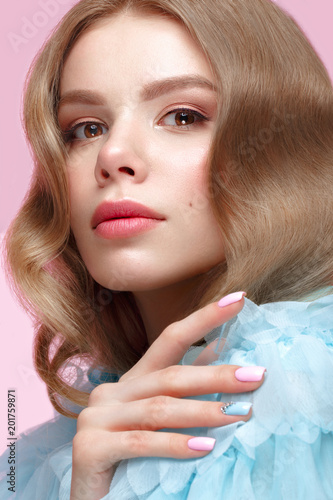 Foto Murales Beautiful girl with light make-up and gentle manicure in blue clothes. Beauty face. Design nails. Photo taken in studio on pink background