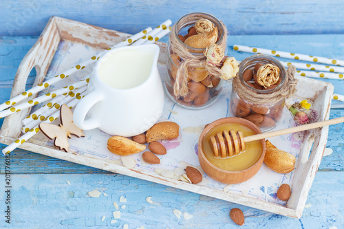 Almonds and jar with milk on the wooden tray