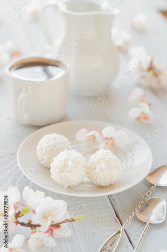 Wall mural Cup of coffee, milk and apricot blossoming branch on white wooden table