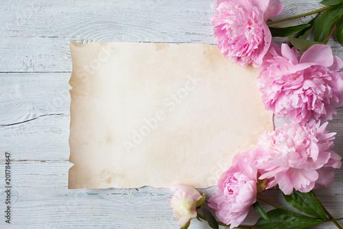 Różowe peonie na drewnianym tle i prześcieradło papier dla gratulacj, zaproszenia