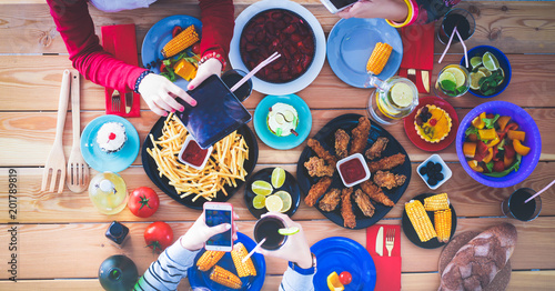 Top view of group of people having dinner together while sitting at wooden table. Food on the table. People eat fast food. - 201789819