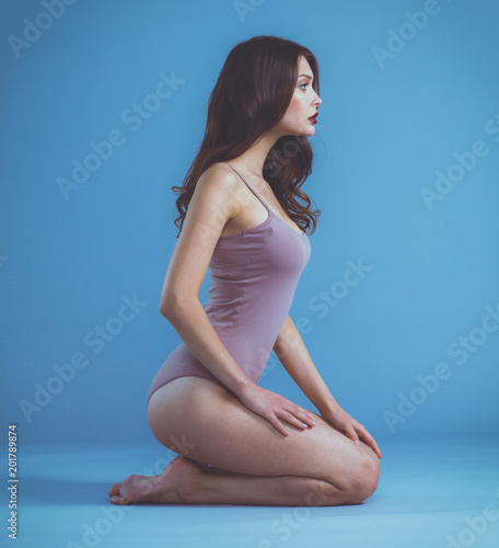 Beautiful barefoot woman sitting on the floor . Beautiful barefoot woman.
