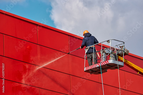 Leinwanddruck Bild Worker wearing safety harness washes wall facade at height on modern building in a crane.