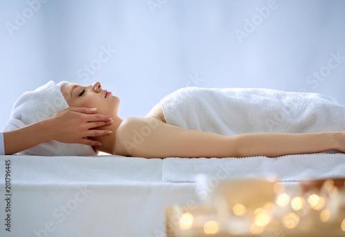 Młodej kobiety lying on the beach na masażu stole, relaksuje z oczami zamykającymi. Kobieta. Salon spa