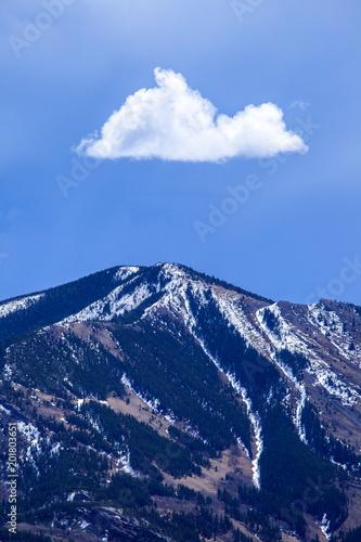 Pojedyncza biała chmura nad szczytem górskim