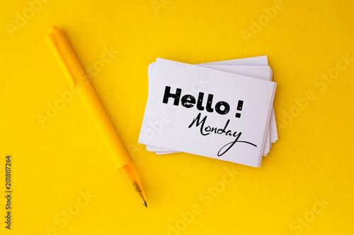 the yellow pen and stacking of  white business card with Hello Monday message on vibrant yellow background , cheerful for happy working time  Monday concept