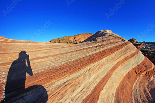 Plexiglas Donkerblauw Photographer sitting on the Fire Wave rock at sunset, Valley of Fire State Park, Nevada, USA