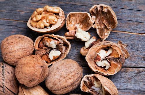 heap of walnuts with nutshell on whooden background