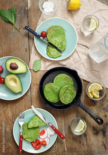 Spinach pancakes with vegetables and water with lemon on a wooden table, top view. Healthy breakfast table concept