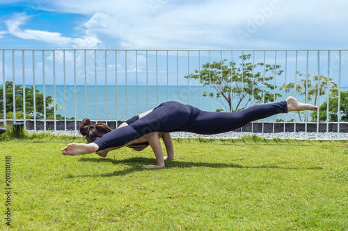 Happy Asian woman wearing black sport wear practice yoga astavakrasana Pose with beautiful sea view,Feeling relax and comfortable,Healthy Concept