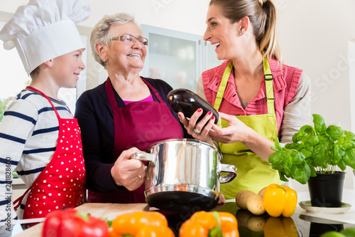 Happy granny, mum and son talking while cooking in kitchen - 201828600