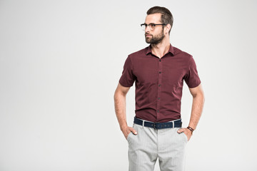 handsome serious man posing in casual closing and glasses, isolated on grey