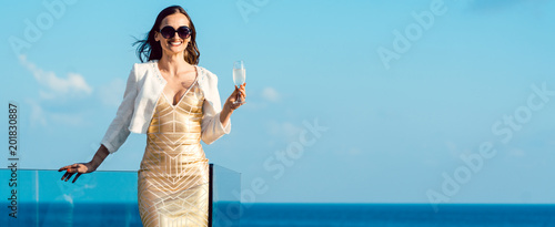 Foto Murales Woman drinking sparkling wine looking over ocean wearing an expensive dress