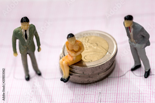 Small toys people are on euro coins and on cardiogram