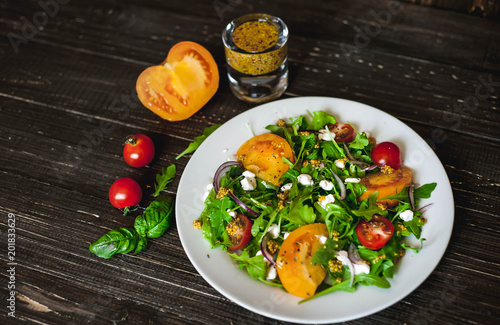 Fresh salad with tomatoes, mixed greens ,nuts, eggs, on wooden background . Healthy food.